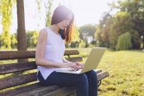 Woman learning at the laptop while sitting on a bench at the park — Stock Photo