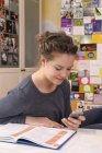 Female pupil with smartphone at her desk — Stock Photo