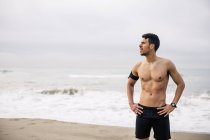 Sportive young man standing on beach — Stock Photo