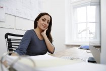Portrait of smiling woman at desk in office — Stock Photo