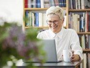 Porträt des lachenden senior Frau mit Laptop zu Hause — Stockfoto