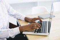 Женщина, использующая ноутбук за столом при исполнении служебных обязанностей — стоковое фото