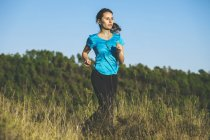 Young female jogger on the move in front of forest — Stock Photo