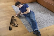 Man with digital tablet lying on floor, cat watching him — Stock Photo