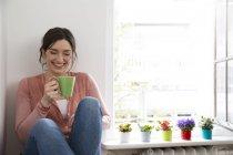 Femme heureuse avec une tasse de café, assis à la fenêtre — Photo de stock