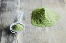 Moringa powder on spoon and wooden table — Stock Photo