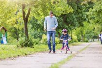 Father accompanying daughter on bike at park — Stock Photo