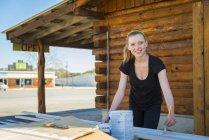 Lächelnde junge Frau beim Bemalen von Balken — Stockfoto