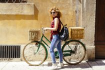 Smiling woman with bicycle in alley — Stock Photo