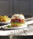 Hamburger sulla piastra e patatine fritte sulla tavola di legno — Foto stock
