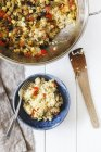 Bowl of vegetable paella and pan on white wood — Stock Photo