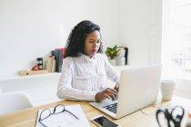 Giovane donna che utilizza il computer portatile in ufficio — Foto stock