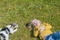Laughing boy lying with Jack Russel Terrier puppy on meadow — Stock Photo