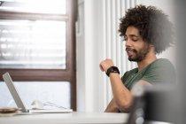 Креативный профессионал смотрит на смартфон в офисе — стоковое фото