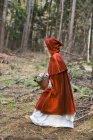 Mascherata ragazza come Cappuccetto rosso in movimento in legno — Foto stock