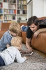 Батько, лежачи на дивані, використовуючи цифровий планшет з синами — стокове фото