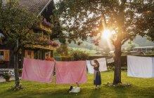 Женщина фермер висит прачечная на линии — стоковое фото