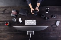 Man sitting at desk with camera — Stock Photo