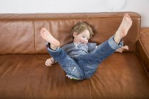 Boy messing around on couch — Stock Photo