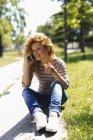 Портрет счастливой женщины, звонящей со смартфона в парке — стоковое фото