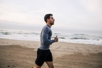 Young man running on sandy beach — Stock Photo