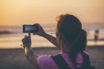 Indonesien, Bali, Frau am Strand fotografieren Sonnenuntergang mit ihrem smartphone — Stockfoto