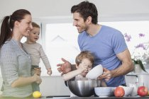 Family with two kids preparing food in kitchen — Stock Photo
