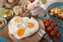 Variation of egg dishes and easter decoration on chopping board over table — Stock Photo