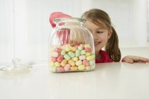 Girl with candy jar choosing one — Stock Photo