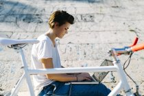 Young woman with bicycle sitting outdoors using laptop — Stock Photo