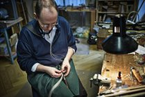 Violin maker repairing a bow in workshop — Stock Photo