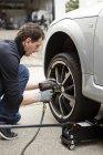 Uomo maturo cambiando pneumatici per auto al giorno — Foto stock