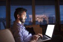 Homem sentado no sofá, usando laptop — Fotografia de Stock