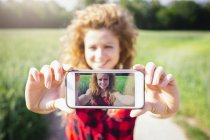 Selfie of smiling woman on display of her smartphone — Stock Photo