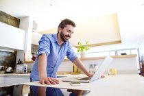 Uomo che lavora in cucina utilizzando il computer portatile — Foto stock