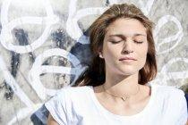 Portrait de jeune femme avec les yeux fermés en face d'un mur — Photo de stock