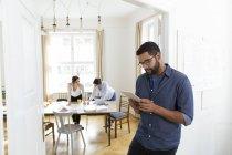 Mann im Büro mit digital-Tablette mit Kolleginnen und Kollegen im Hintergrund — Stockfoto