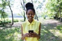 Ritratto di giovane donna sorridente in natura guardando il suo smartphone — Foto stock