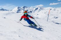 Boy in helmet and skiwear skiing in sunny day on snowy mountain slope — Stock Photo