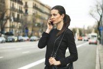 Mujer joven con en el teléfono en la calle de la ciudad - foto de stock