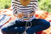 Donna seduta su una coperta su un prato utilizzando lo smartphone — Foto stock