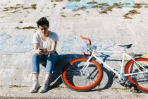 Jeune femme avec vélo et téléphone portable — Photo de stock