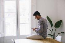 Jungunternehmer am Schreibtisch sitzen und mit smartphone — Stockfoto