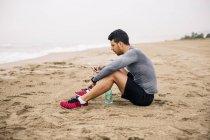 Lepilemur giovane con cellulare e bottiglia bevente che si siede sulla spiaggia sabbiosa — Foto stock