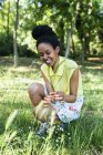 Portrait of smiling young woman picking grasses — Stock Photo