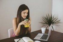 Mujer joven bebiendo jugo mientras está sentado en el escritorio con el ordenador portátil en casa - foto de stock