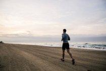 Молодой человек бежит по песчаному пляжу — стоковое фото