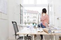 Femme assise sur la table au bureau et téléphonant — Photo de stock