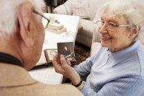 Старшая женщина показывает мужу свою старую фотографию — стоковое фото