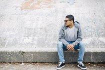 Giovane seduto su un muro indossando una felpa con cappuccio — Foto stock